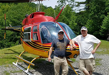 Bill Macchio standing next to a helicopter with son Drew, the pilot